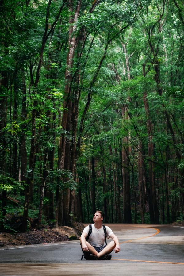 Man sits on road, Bilar Man-Made Forest, Bohol, Philippines. Man with backpack sits on road through green Bilar Man-Made Forest, Bohol, Philippines stock images