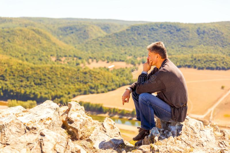 A man sits on a rock on the High Mountain and looks out into the distance on the Ural Mountains. An autumn sunny day stock photo