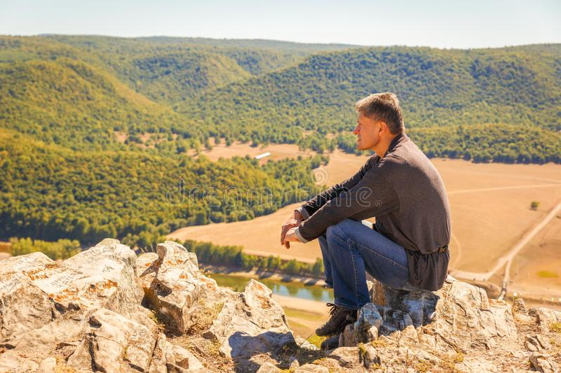 A man sits on a rock on the High Mountain and looks out into the distance on the Ural Mountains,. An autumn sunny day royalty free stock images