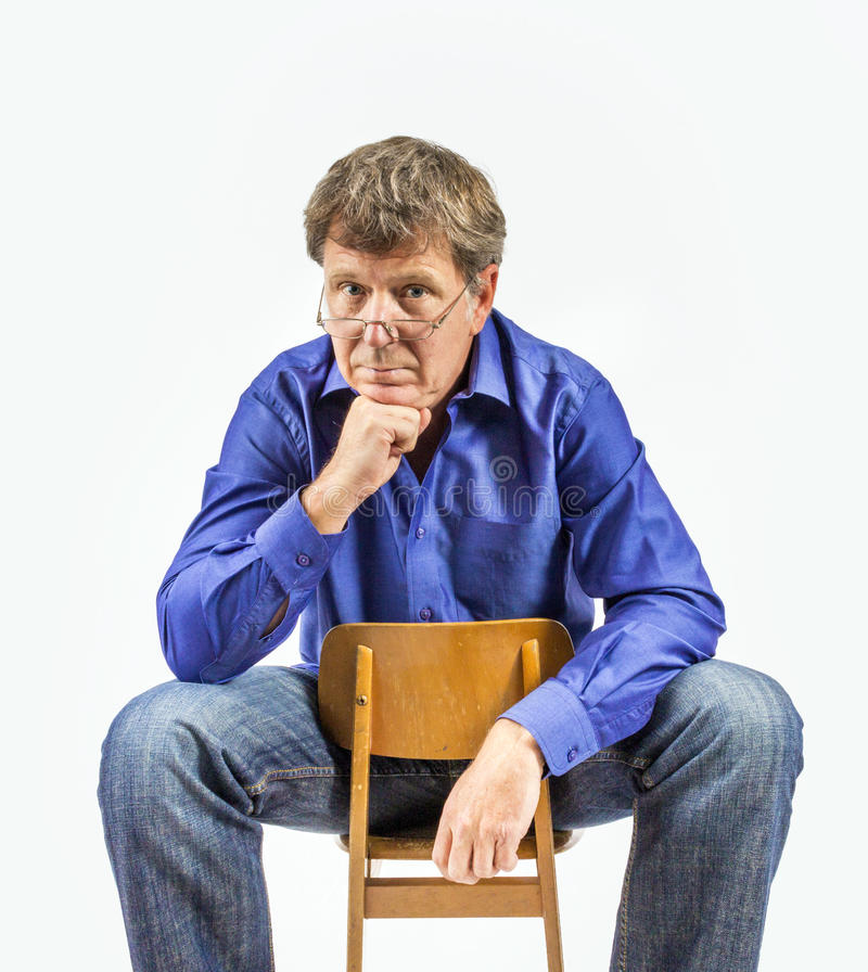 Man sits on a small wooden chair. Handsome man sits on a small wooden chair and poses royalty free stock image