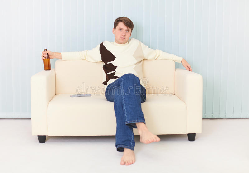 [Image: man-sits-sofa-beer-bottle-hand-12210704.jpg]
