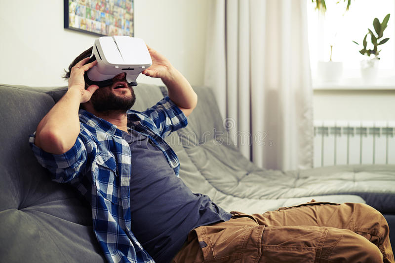 Man sits on sofa and having fun using white VR headset. Young Caucasian man sits on sofa and having fun using white VR headset glasses stock photo
