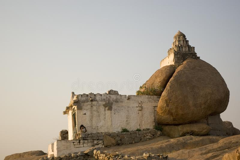 A man sits at a stone Hindu unique temple of Shiva in Hampi, India at dawn royalty free stock image