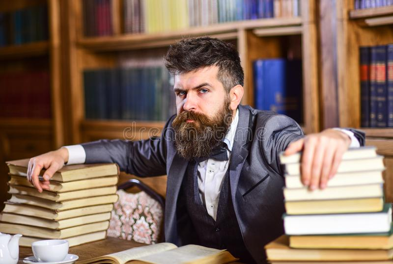 Man sits at table with many books. Mature man has serious face and looks confident. Successful study, education, hard work, intellectual work, confidence stock photography