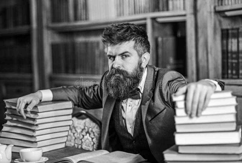 Man sits at table with many books. Mature man has serious face and looks confident. Successful study, education, hard work, intellectual work, confidence royalty free stock images