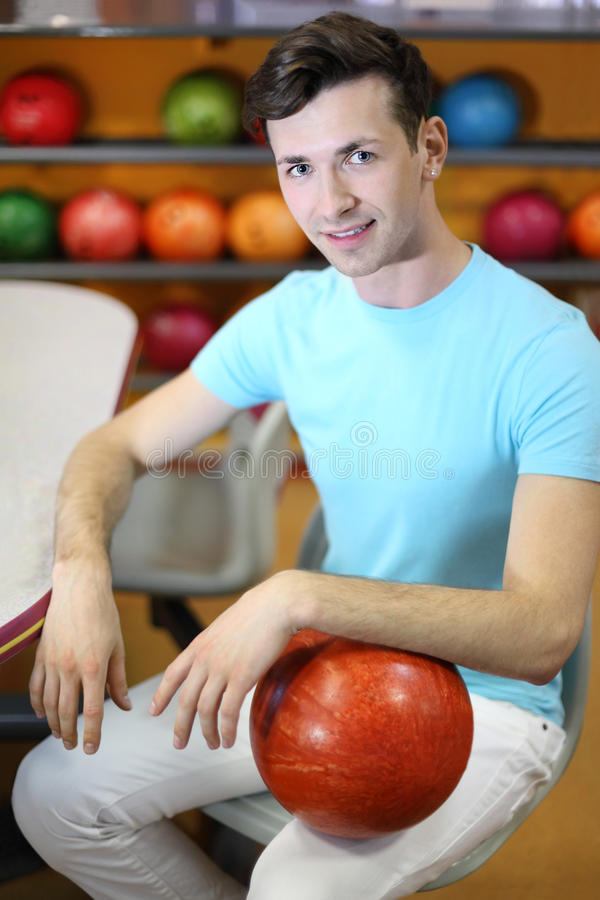 Download Man Sits At Table Near Shelves With Balls Stock Photo - Image: 25150558