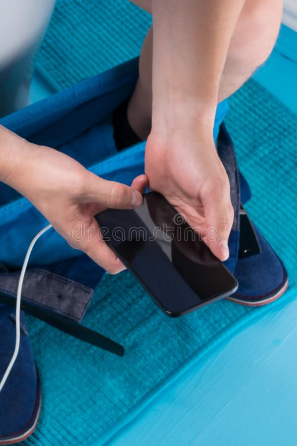 A man sits in a toilet for a long time with a charging smartphone, close-up royalty free stock image