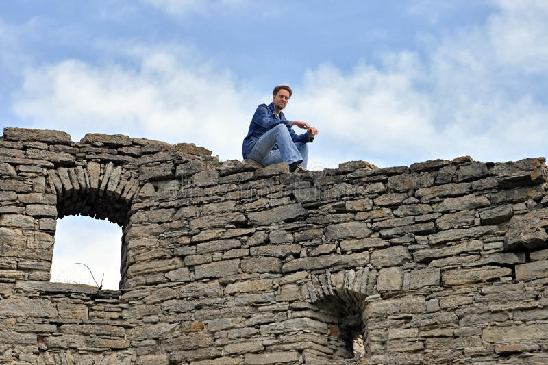 Man sits on the top old castle wall royalty free stock images