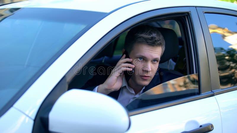 Man sitter i bil, spionerar fru med älskare och pratar telefon med mördare. arkivfoto