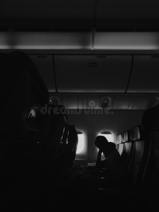 Man sitting against window in plane and reading book. Silhouette of man sitting against small window of airplane with book on his lap. Almost no light in the stock image