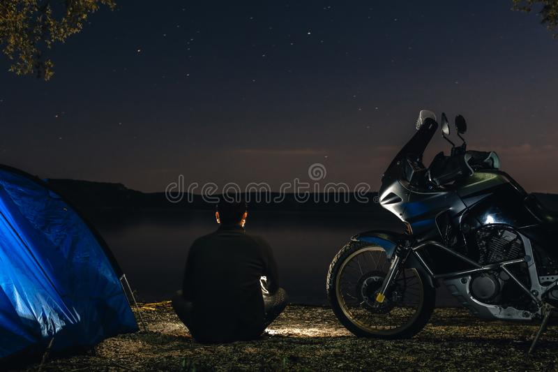 Man is sitting alone on beach in darkness and look othe sky Blue Camping Tent Illuminated Inside. Night Hours Campsite. Recreation. And Outdoor. adventure stock photo