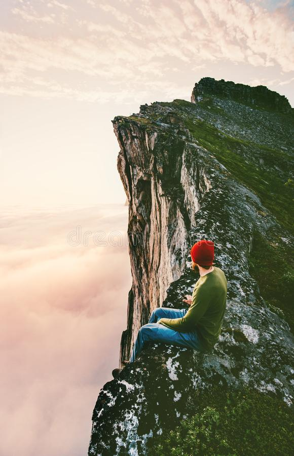 Man sitting alone on the edge mountain ridge above clouds royalty free stock photos