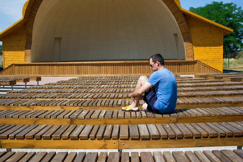 The man sitting alone in her back among many benches royalty free stock image