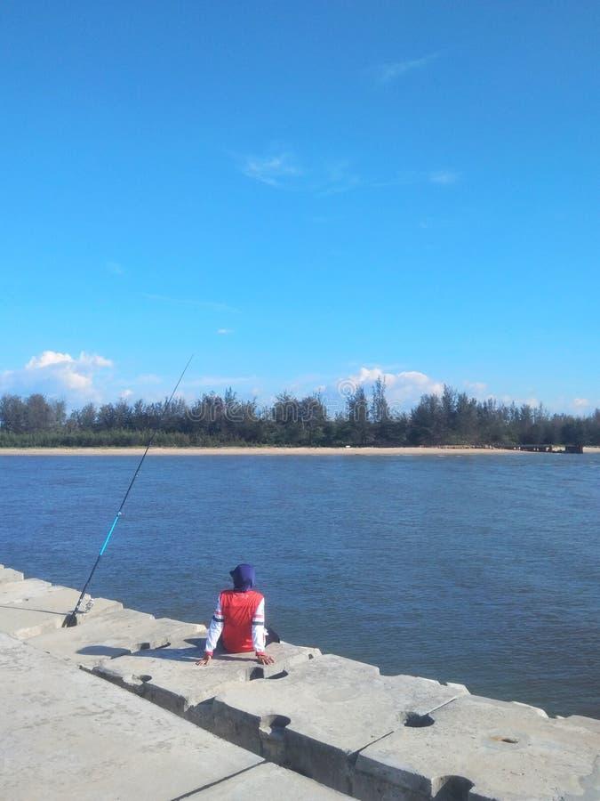 Man sitting alone on pier fishing stock image