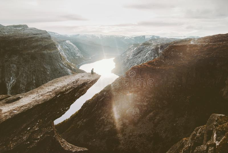 Man sitting alone on Trolltunga cliff edge in Norway. Travel adventure lifestyle active vacations getaway outdoor sunset mountains over lake landscape stock photo