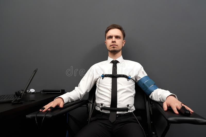 Man sitting with attaching sensors on fingers and  body. royalty free stock photo