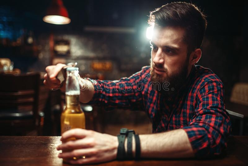 Man sitting at the bar counter and opens bottle. Sad man sitting at the bar counter and opens the bottle with alcohol beverage. Male person in pub, alcoholism stock photography
