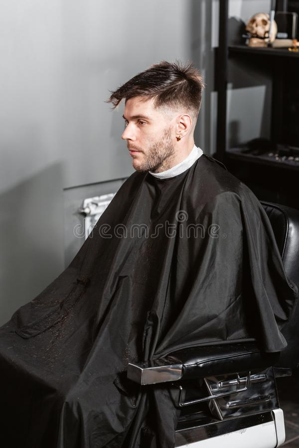 Man sitting in a Barber chair. Master cuts hair and beard of men in the barbershop, hairdresser makes hairstyle for a stock photography