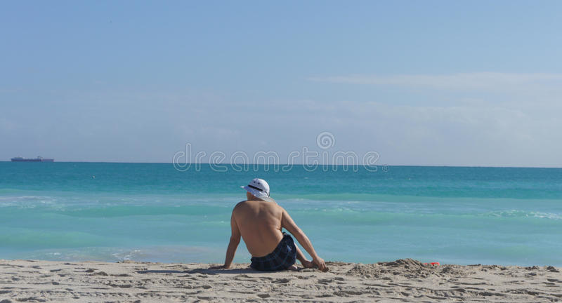 Man sitting on the beach stock photography