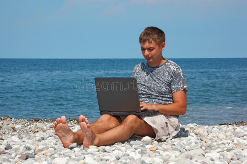Man Sitting On Beach With Laptop On His Knees Stock Photography