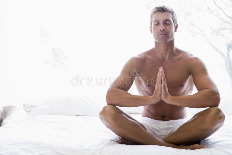 Man sitting on bed meditating. With legs crossed stock photography
