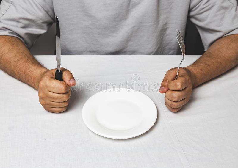 Man sitting behind a table with fork and knife in hands and empty plate, Time to eat - therapeutic fasting concept. Waiting, hungry, lunch, holding, expression royalty free stock photography
