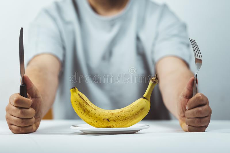 man sitting behind a table with fork and knife in hands and a fresh banana on a plate on a white table , Time to eat - healthy royalty free stock image