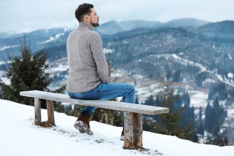 Man sitting on bench and enjoying mountain, space for text. Winter vacation. Man sitting on bench and enjoying mountain landscape, space for text. Winter stock photo