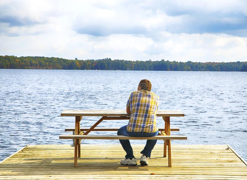 Man sitting on a bench in front of a lake stock image