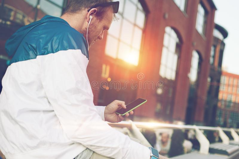 Man sitting on the bench with mobile phone and typing message. Outdoors royalty free stock photography