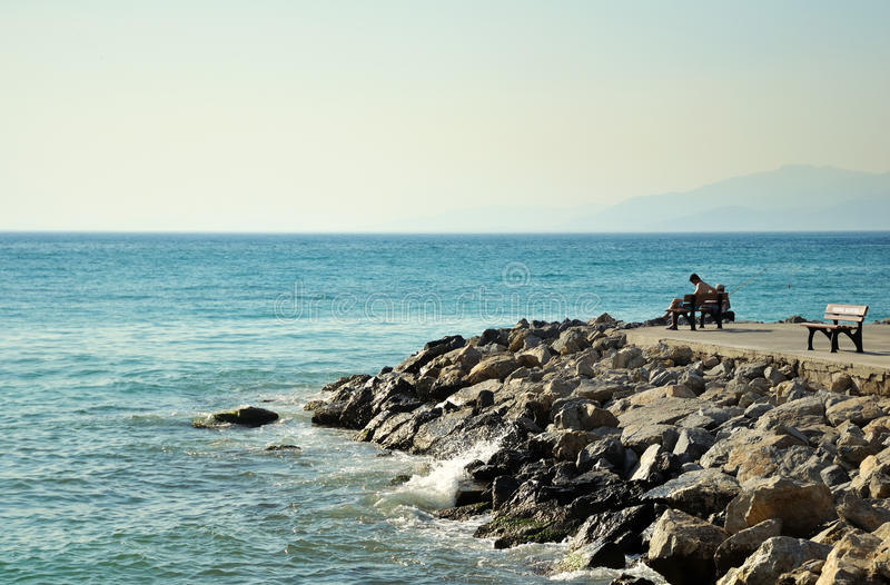 Man sitting on bench by sea, lateral view stock photo