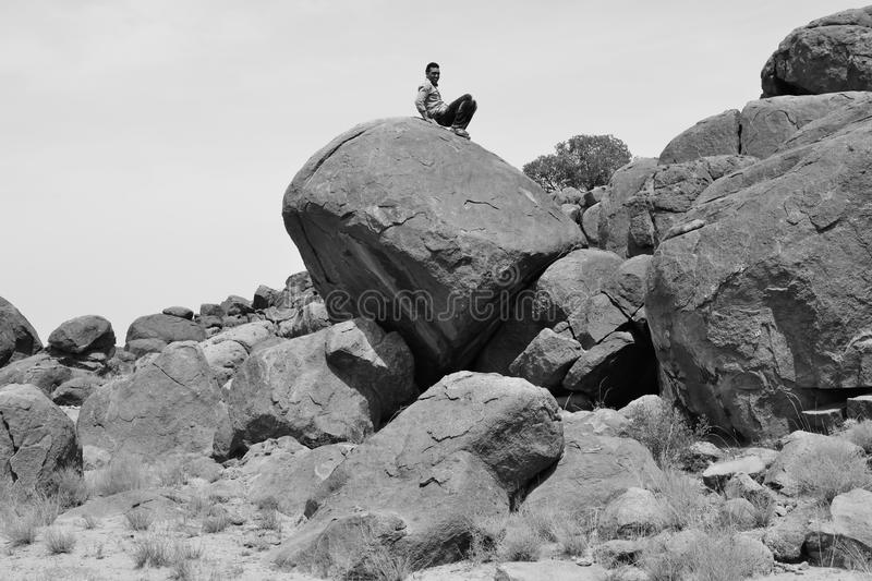 Man sitting on a big rock in the desert -B&W-. Man sitting on a pile of rocks in south Morocco royalty free stock photos