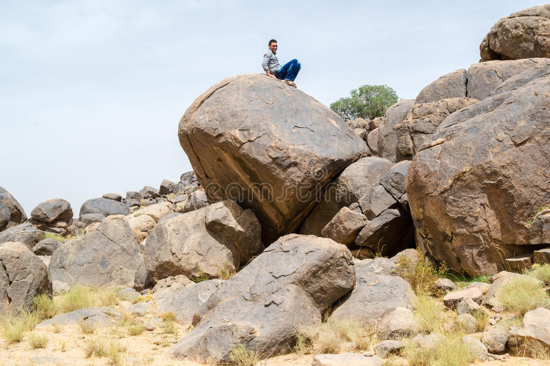Man sitting on a big rock in the desert. Young sitting on a big rock near other rocks in the desert stock photos