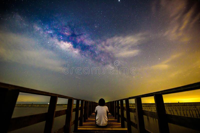 The man sitting at the bridge with milky way royalty free stock image