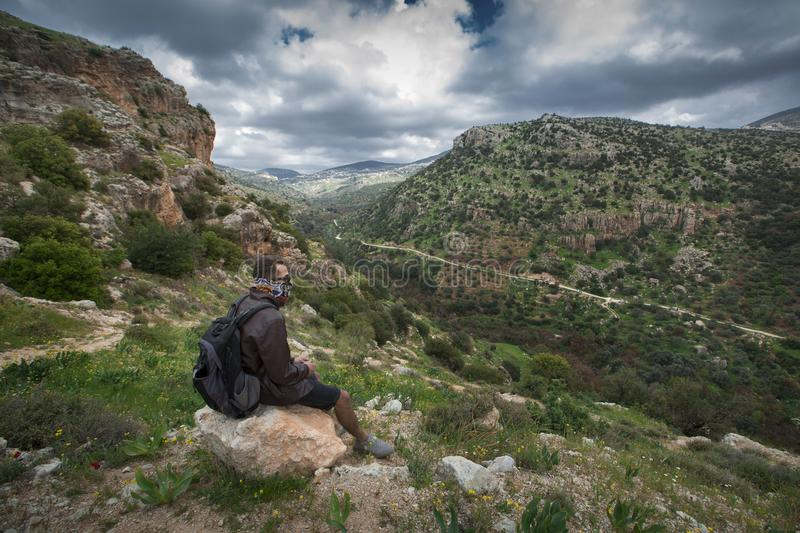 Man Sitting on Brown Boulder Top on Hill royalty free stock photos