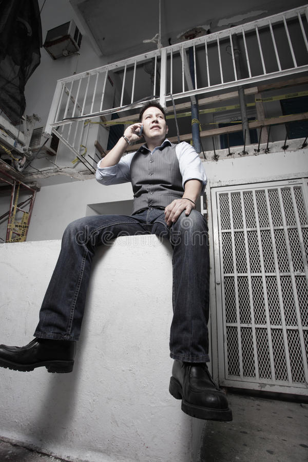 Man Sitting By A Building Under Construction Stock Images