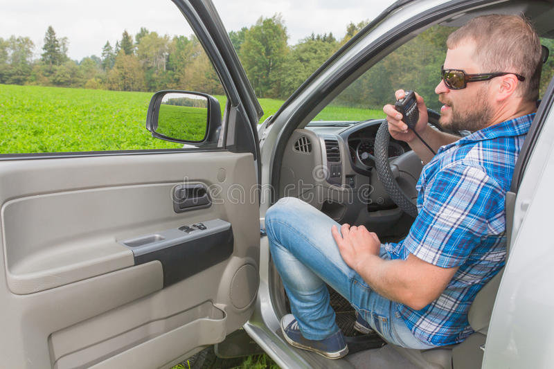 Man sitting in a car. On driver's place and talking handheld transceiver stock images