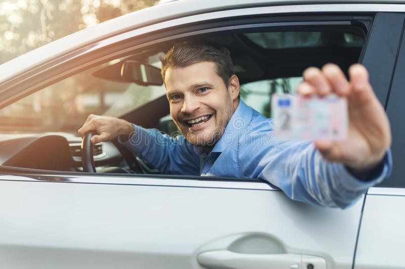 Man sitting in the car and showing his driver license out of car window royalty free stock photography