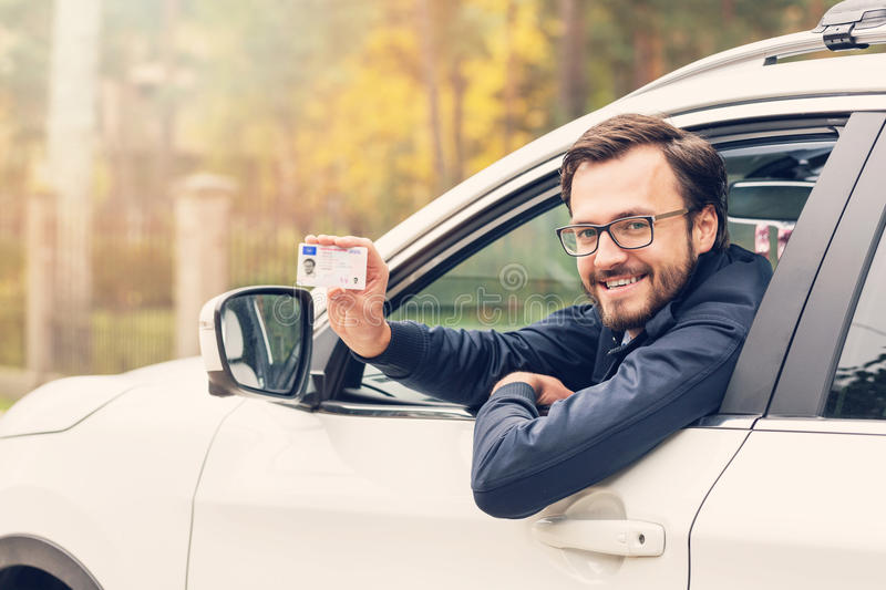 Man sitting in the car and showing his driver license royalty free stock image