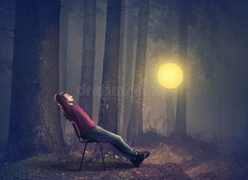 Man sitting on chair in the forest. Watching fairy light globe royalty free stock image