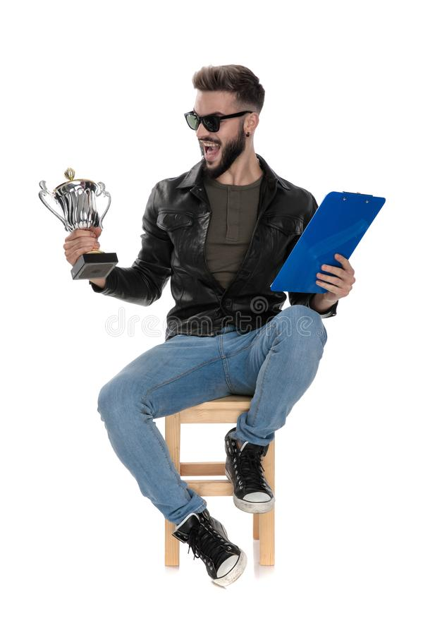 Man sitting on chair holding trophy and blue folder royalty free stock images