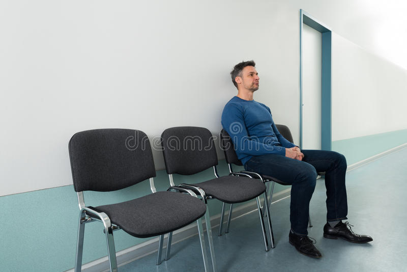 Man sitting on chair in hospital. Portrait Of A Mid-adult Man Sitting On Chair In Hospital royalty free stock photo