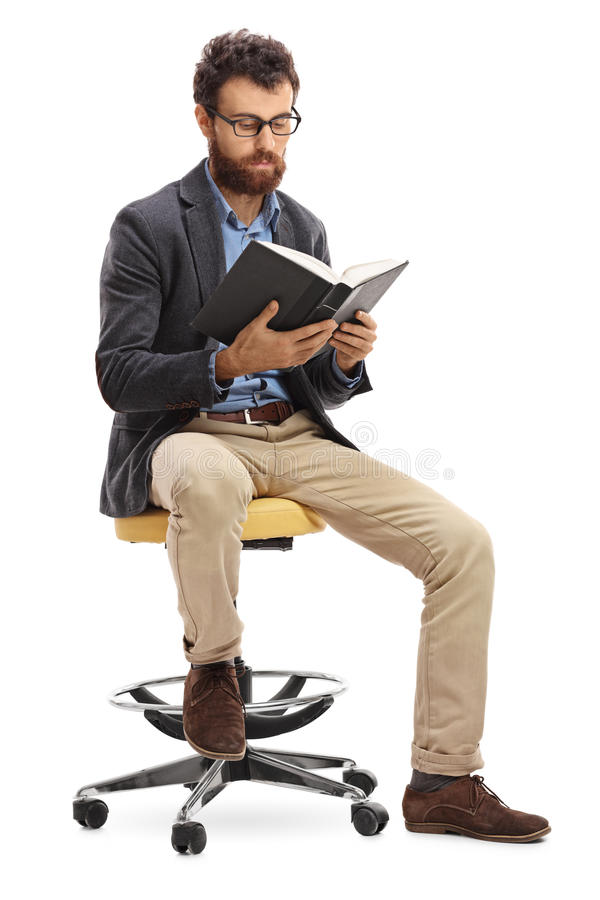 Man sitting on a chair and reading a book. Isolated on white background royalty free stock photography