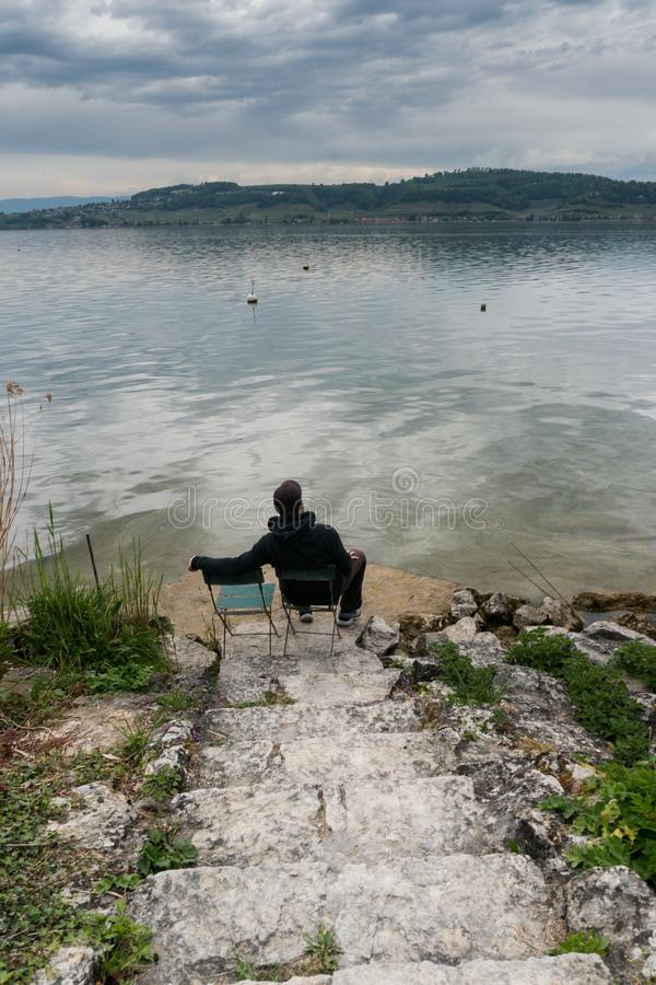 Man sitting on a chair at the shores of a beautiful lake on a calm spring evening with rock stairs leading down to him royalty free stock photography