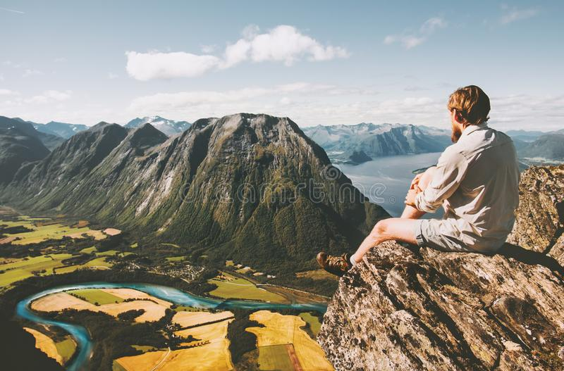 Man sitting on cliff edge relaxing with aerial mountains landscape. Travel lifestyle adventure vacations in Norway traveler thinking alone stock image