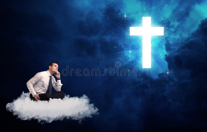 Man sitting on cloud lokking at a cross. Caucasian businessman sitting on a white fluffy cloud looking and wondering at a big bright glowing cross royalty free stock image