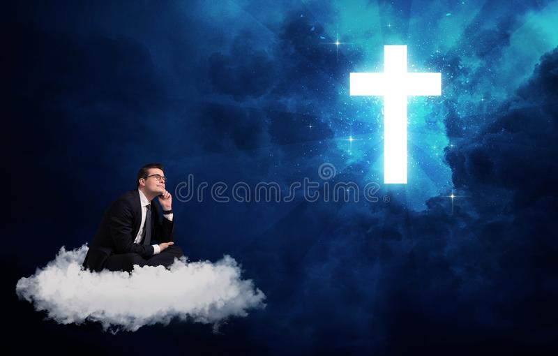 Man sitting on cloud lokking at a cross. Caucasian businessman sitting on a white fluffy cloud looking and wondering at a big bright glowing cross stock photo