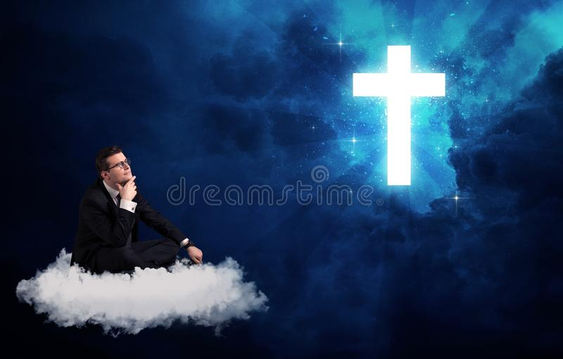 Man sitting on cloud lokking at a cross. Caucasian businessman sitting on a white fluffy cloud looking and wondering at a big bright glowing cross stock images
