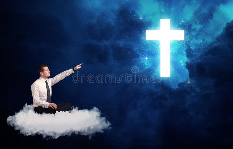 Man sitting on cloud lokking at a cross. Caucasian businessman sitting on a white fluffy cloud looking and wondering at a big bright glowing cross royalty free stock images