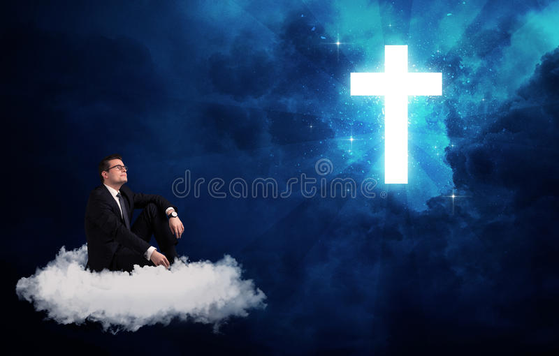 Man sitting on cloud lokking at a cross. Caucasian businessman sitting on a white fluffy cloud looking and wondering at a big bright glowing cross royalty free stock photos